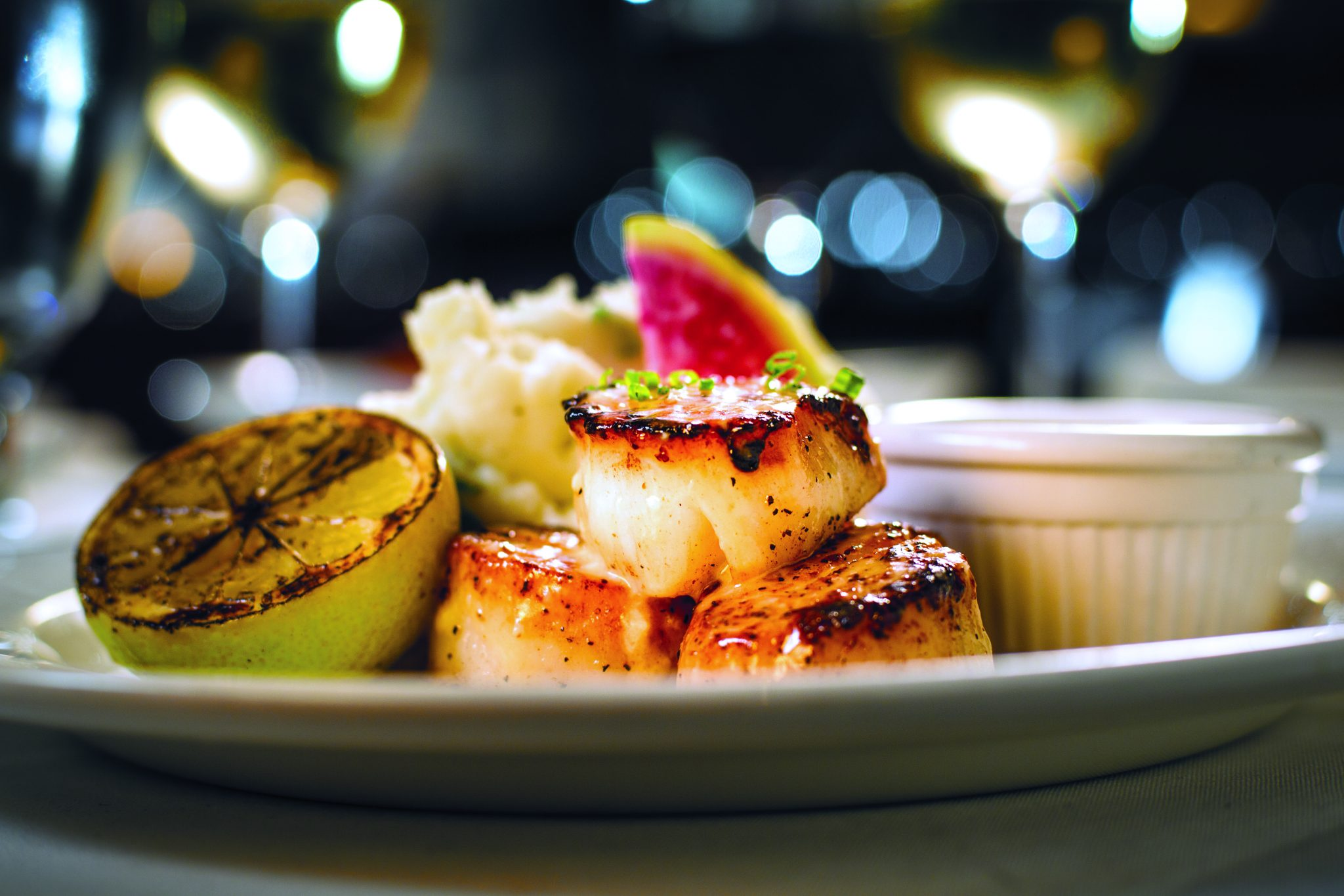 picture of NEW ENGLAND PAN-SEARED SCALLOPS garnished with a lemon