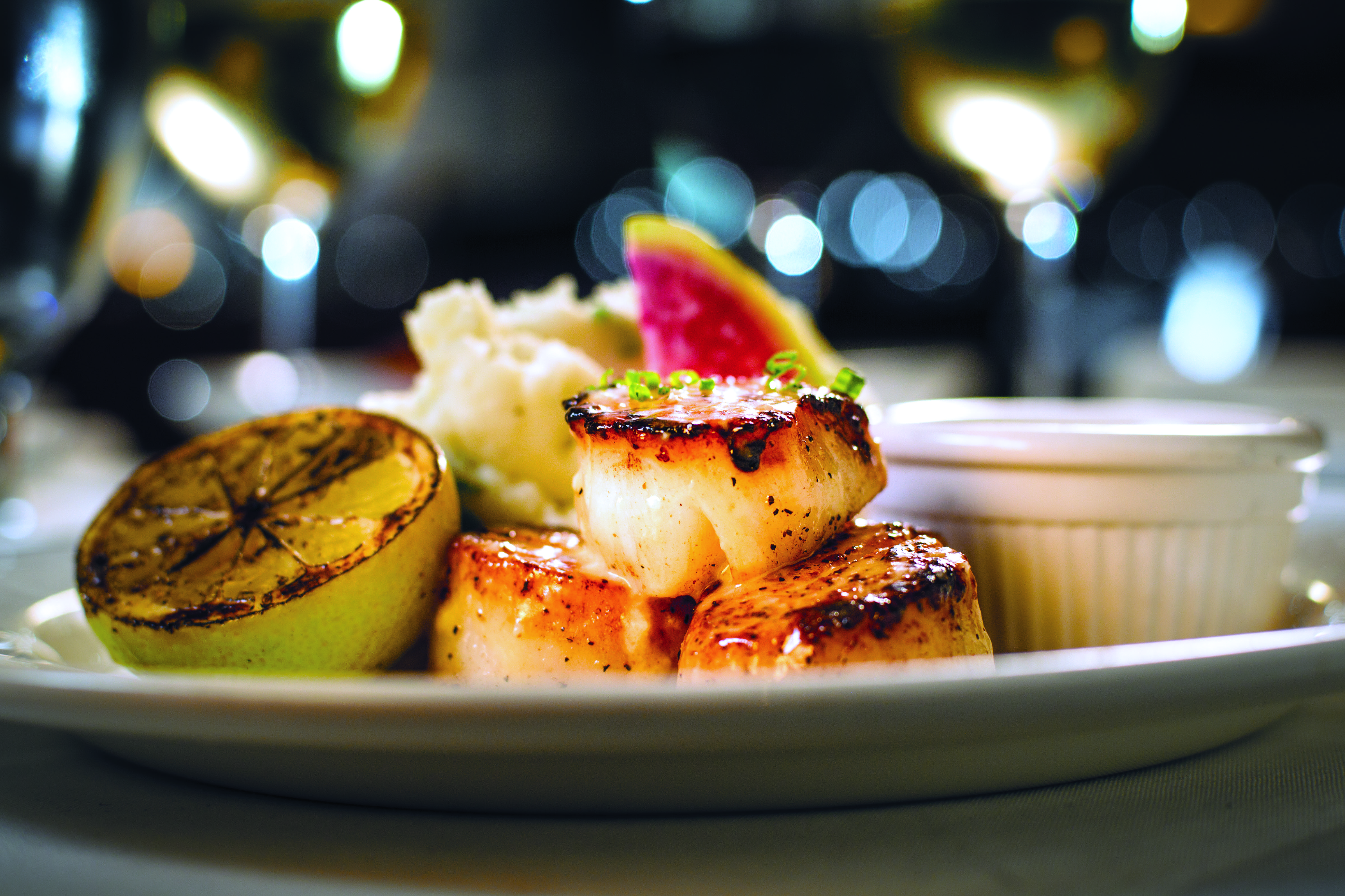 NEW ENGLAND PAN-SEARED SCALLOPS garnished with a lemon