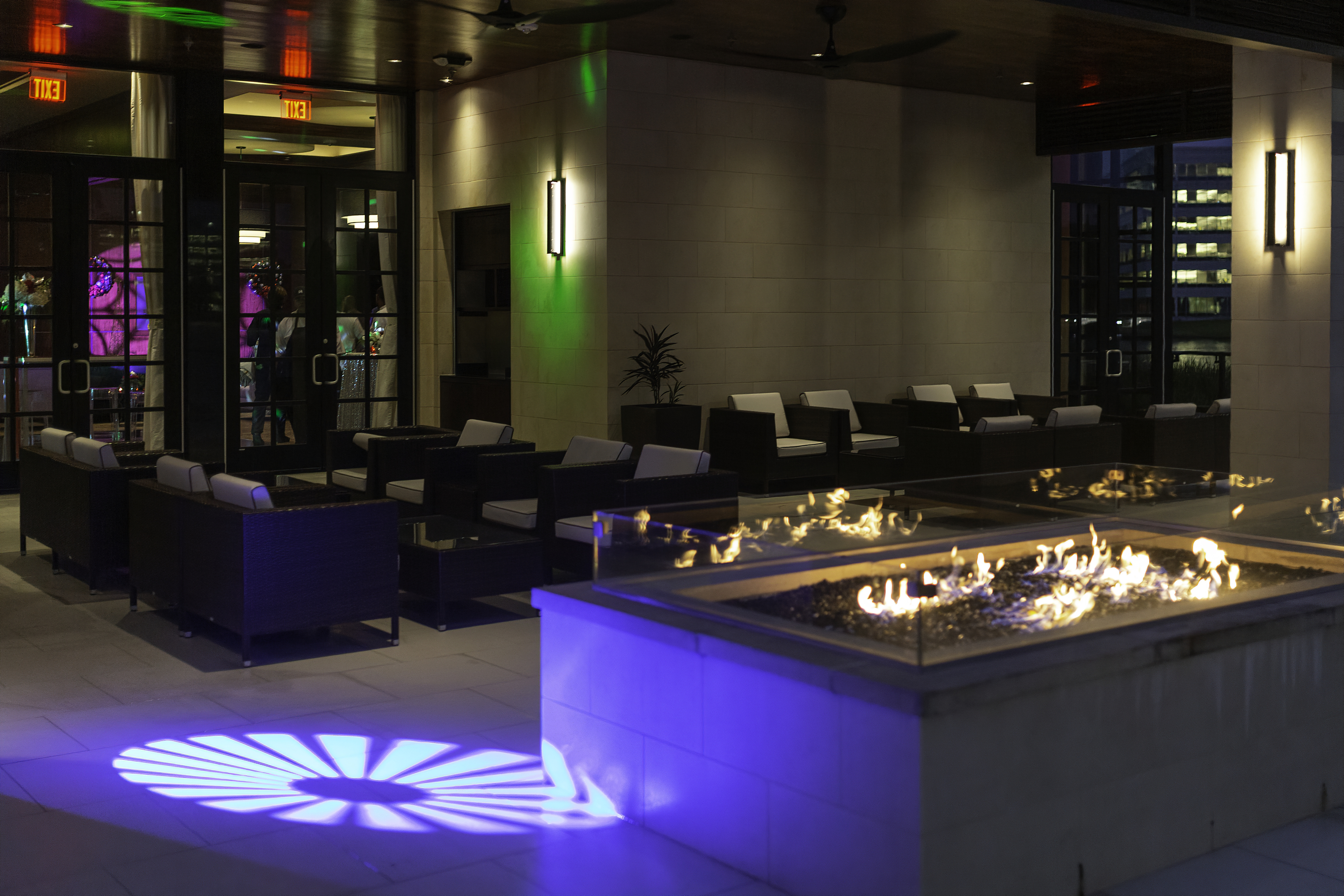 picture of Truluck's Woodlands private dining event on the outdoor terrace. Outdoor lounge style chairs and tables are surrounded by a luxurious gas fire pit and specialty lighting that was brought in to enhance the vibe.