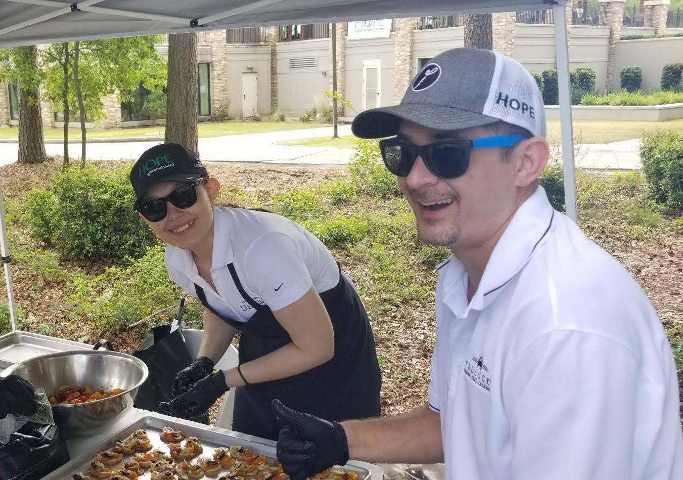 picture of Our staff smiling as they serve food outdoors to community members