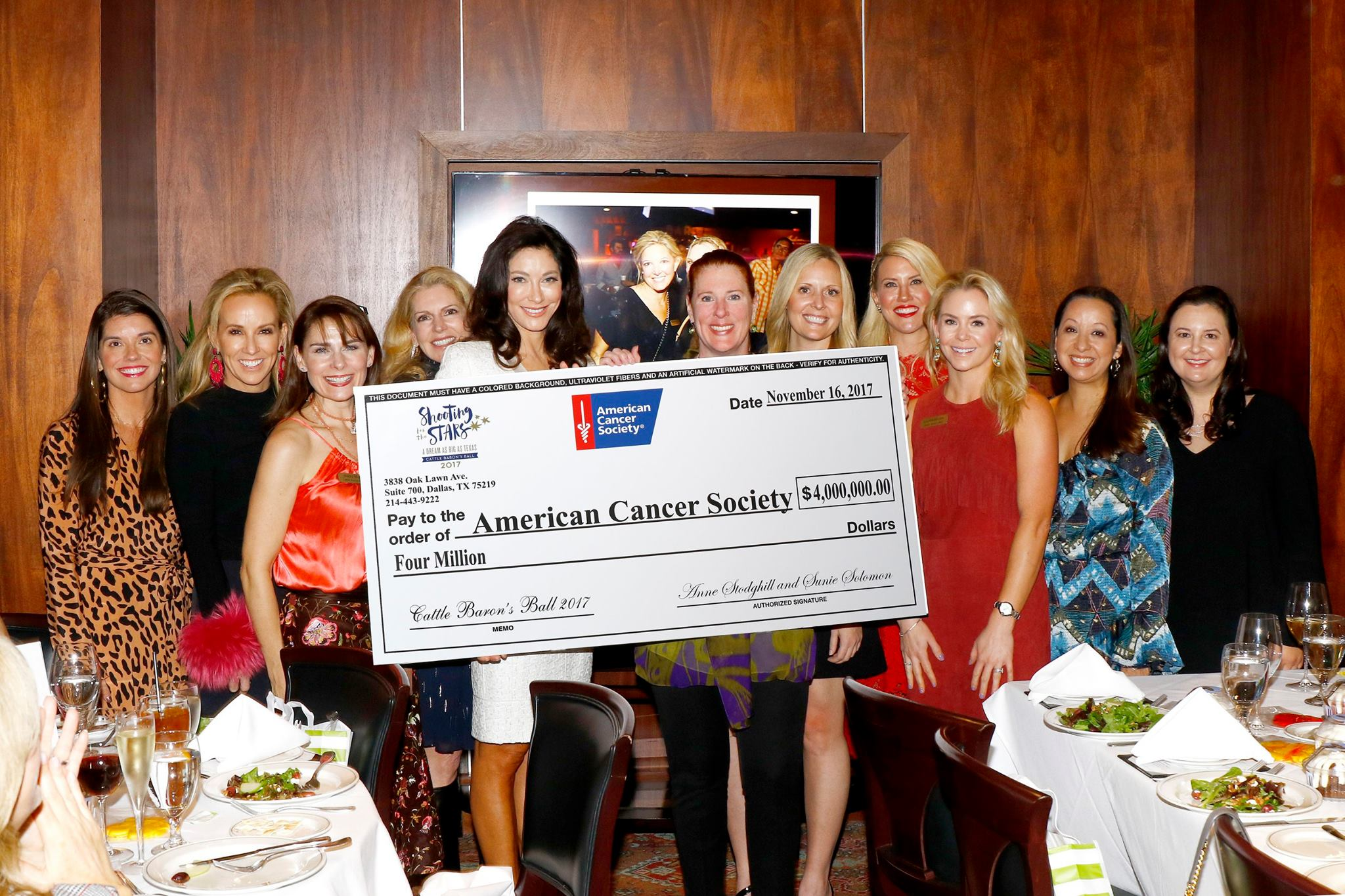 A group of women posing around a charitable donation of four million dollars to the American Cancer Society