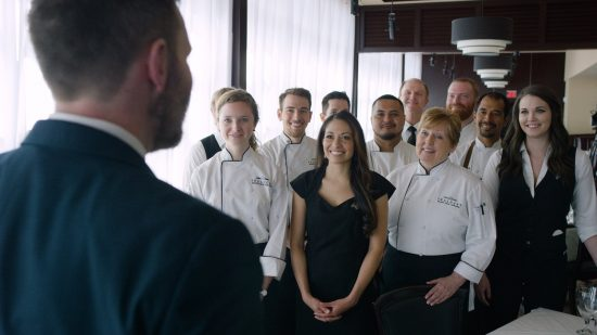 picture of Team of Truluck's staff and chefs smile while listening to head manager