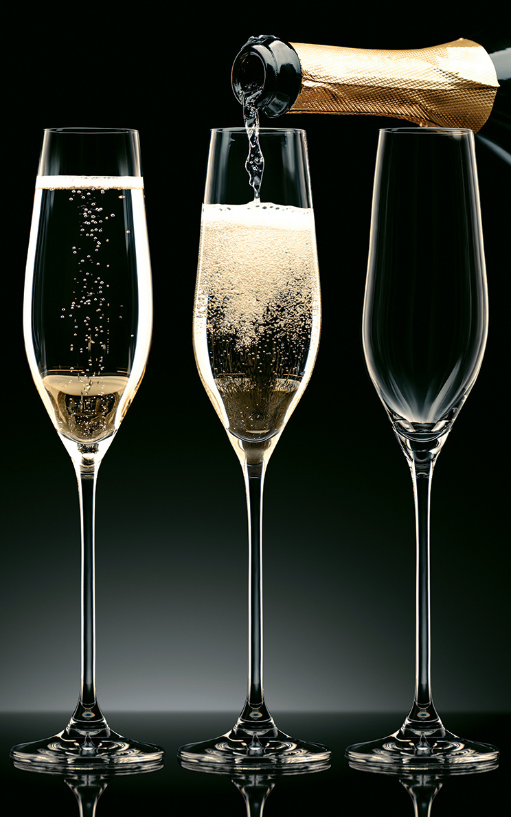 Three champagne glasses being filled up