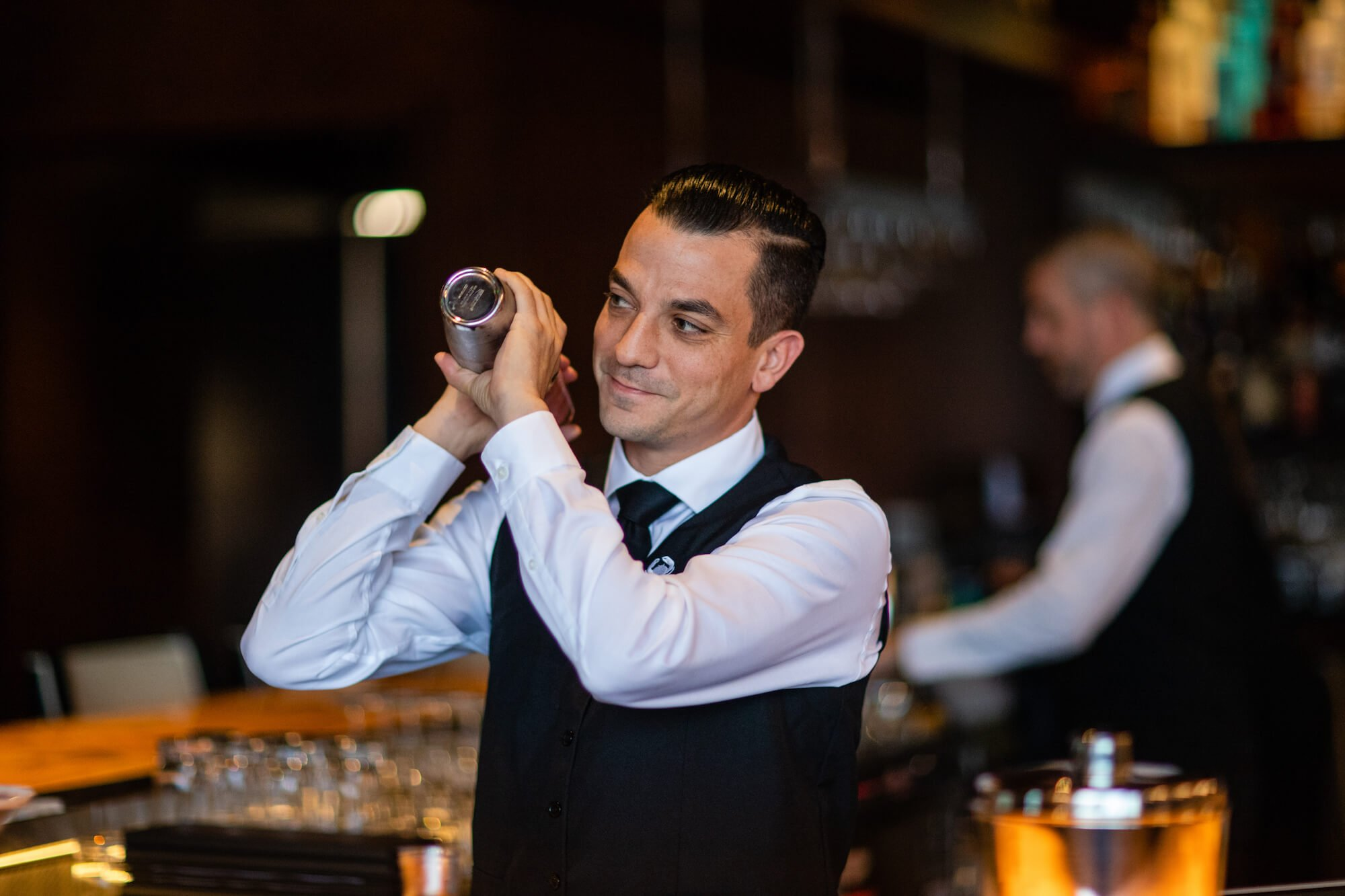 A Truluck's bartender shaking a cocktail shaker with a smile