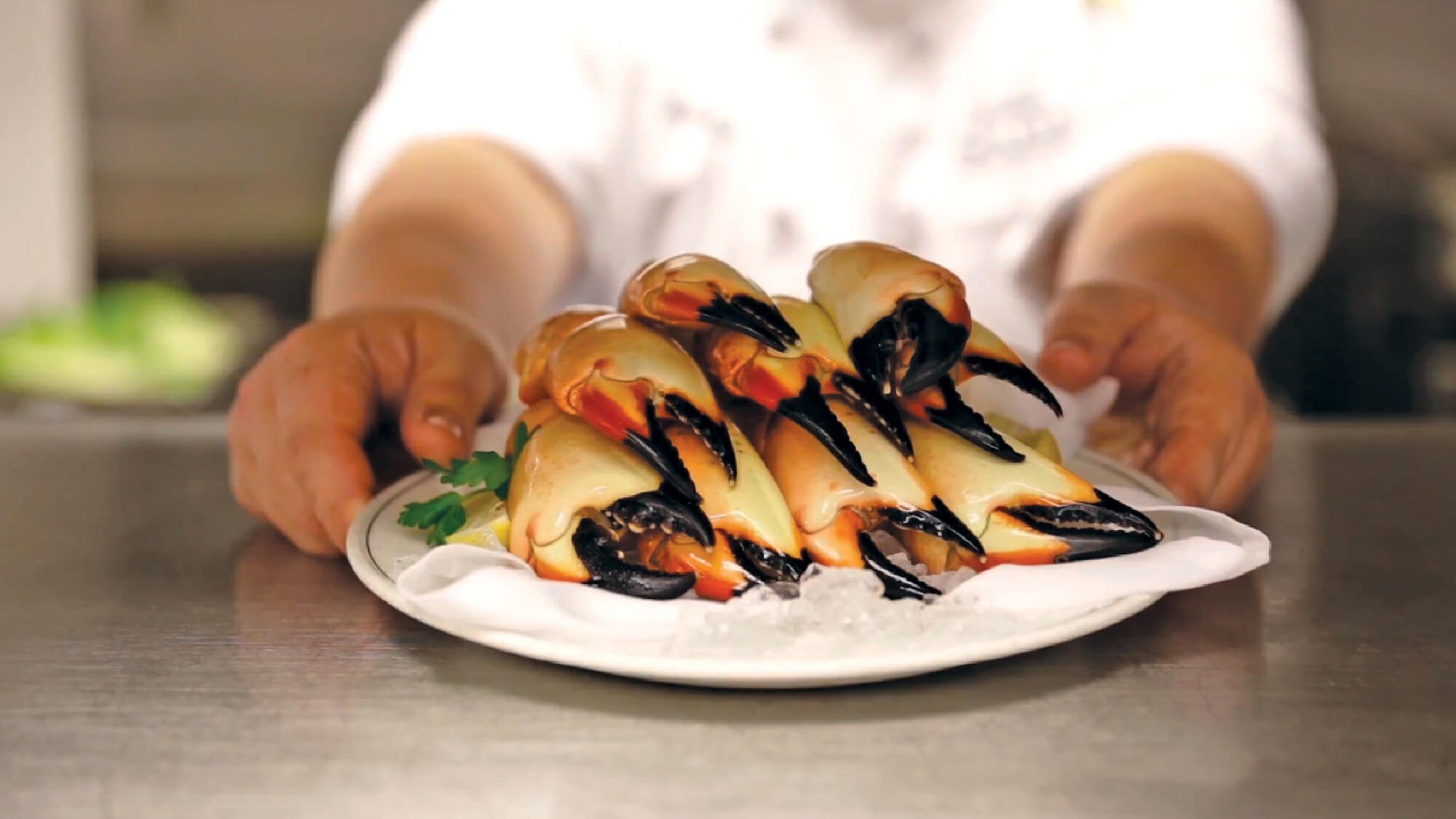 Florida Stone Crab claws on a plate, being served by a Truluck's chef