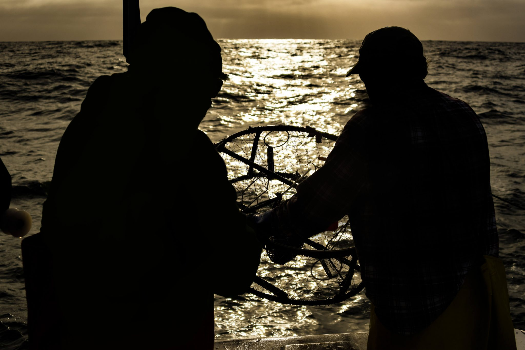 picture of Two crabbers, in silhouette at sunrise
