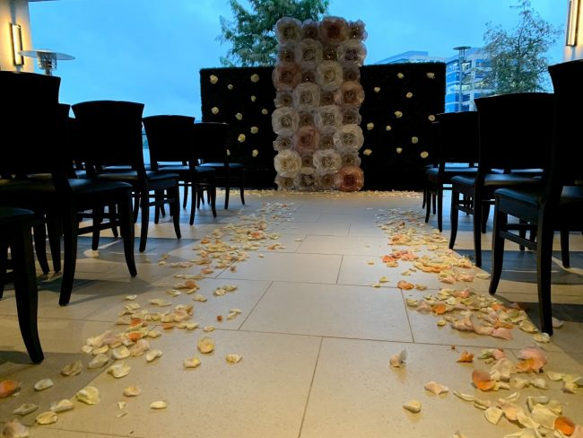 picture of Truluck's Woodlands wedding event with a floor to ceiling paper flower installed background for the couple to marry in front of. Chairs are setup in rows for the ceremony overlooking the water.