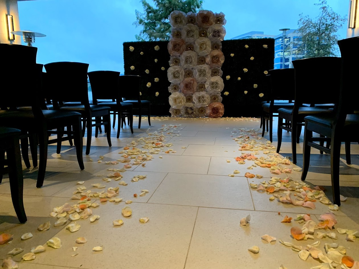 Truluck's Woodlands wedding event with a floor to ceiling paper flower installed background for the couple to marry in front of. Chairs are setup in rows for the ceremony overlooking the water.