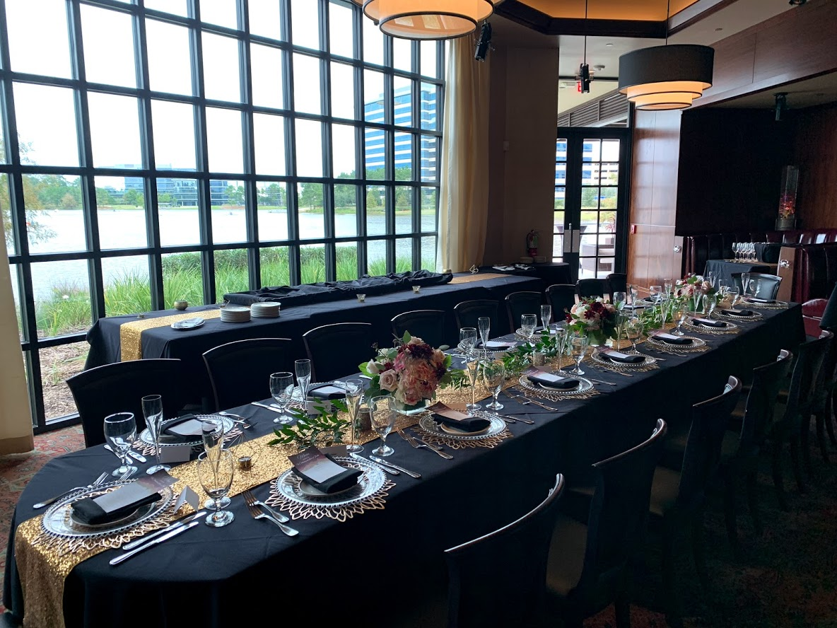 Truluck's Woodlands private dining event with all black linen and gold accents. Table centerpieces are deep purple Dahlias with dusty rose colored roses. This is a long great table for all to enjoy together.