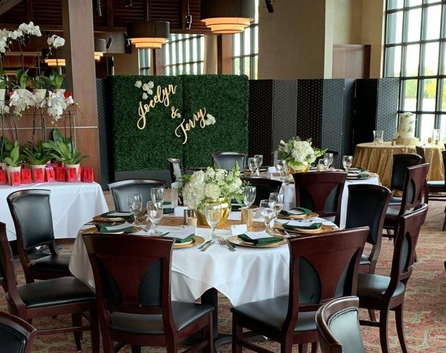 picture of Truluck's Woodlands private dining event featuring orchid take away gifts, a beautiful green hedge with the bride and grooms names made out of wood and painted in gold to hang on the hedge. In the corner is a cake table dressed in gold sequin linen with a 3 tiered white wedding cake. Table accents are gold with deep forest green and white roses.