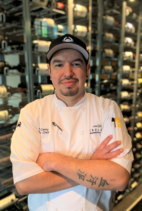 picture of Chef Michael Cerny in front of the wine wall at the restaurant