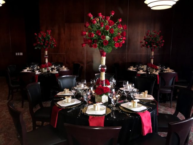 picture of Truluck's Woodlands private event with very dramatic black sequin linens with red satin accents including tall floral centerpieces full of red roses with a take away box of chocolates.