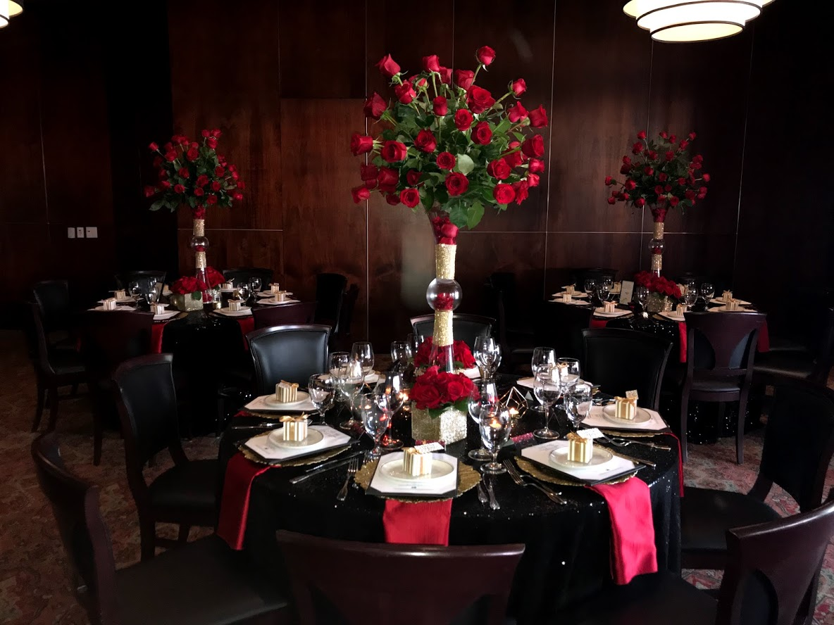 Truluck's Woodlands private event with very dramatic black sequin linens with red satin accents including tall floral centerpieces full of red roses with a take away box of chocolates.