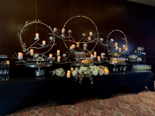 picture of Truluck's Woodlands private event with a magical wine display to include 3 large silver rings with lots of white pillar candles. The table is setup as a wine tasting station with various red, white and sparkling varietals
