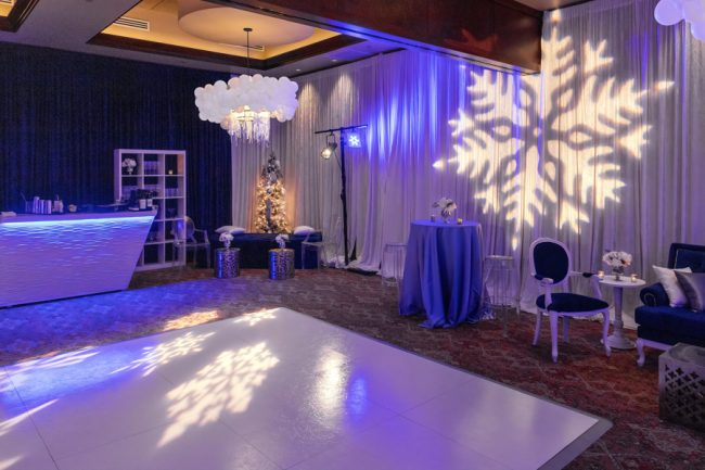 picture of Truluck's Woodlands Winter Wonderland holiday celebration to include a white dance floor, white bar that is lit in bluish light. The ceiling lamps were dressed in silver tinsel and white balloons. Accent furniture in royal blue and white was brought in and snowflake gobos covered the space. The walls were draped in royal blue and white with up lighting and a silver and white Christmas tree is in the background.