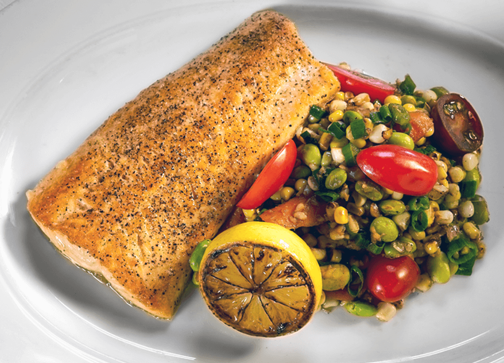 Fresh fish served with a fresh lemon ready to squeeze and paired with a fresh corn salad with tomatoes, lima beans, and green onion