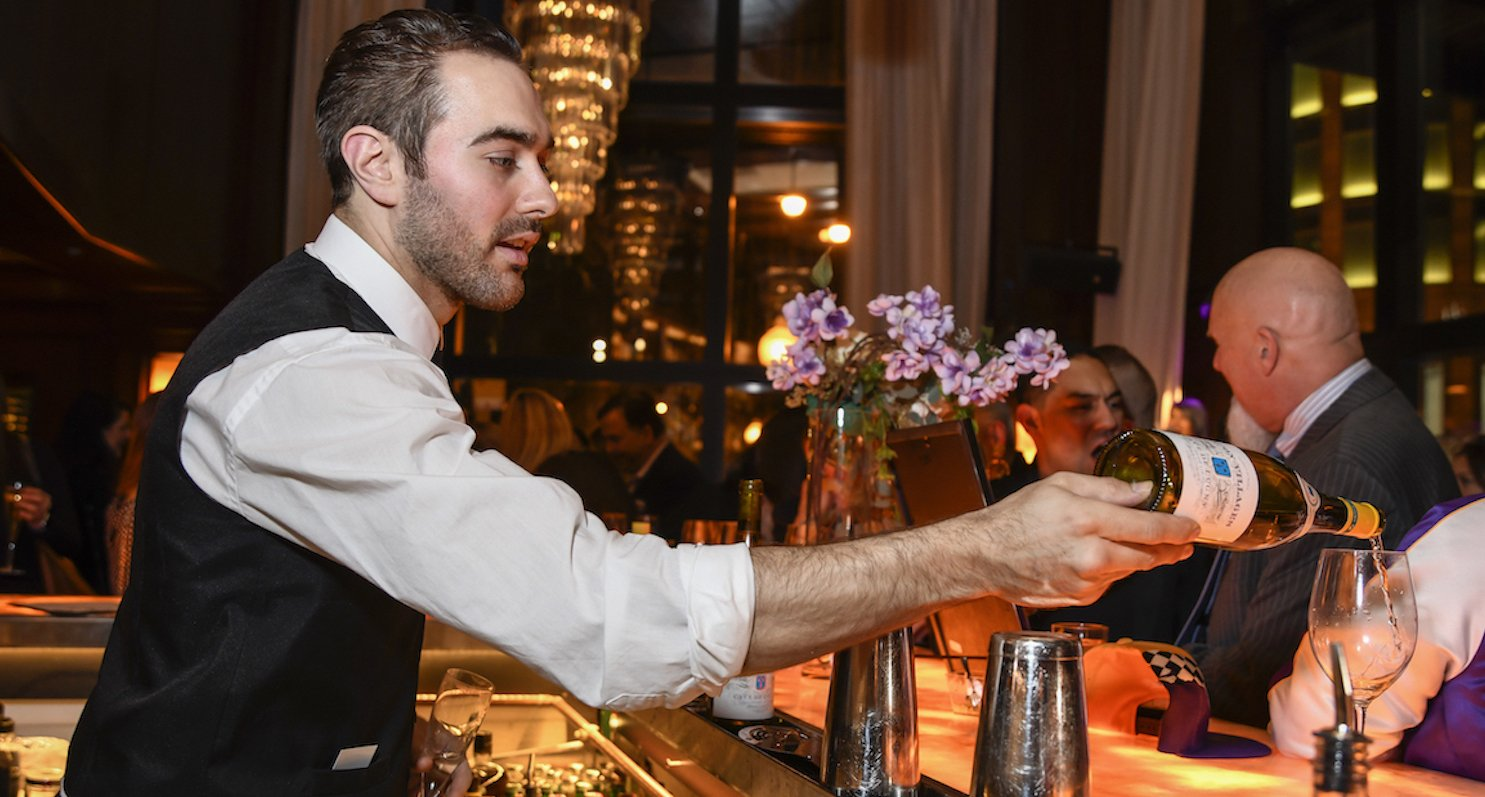 A bartender skillfully pours a glass of white wine, as a party takes place around the bar