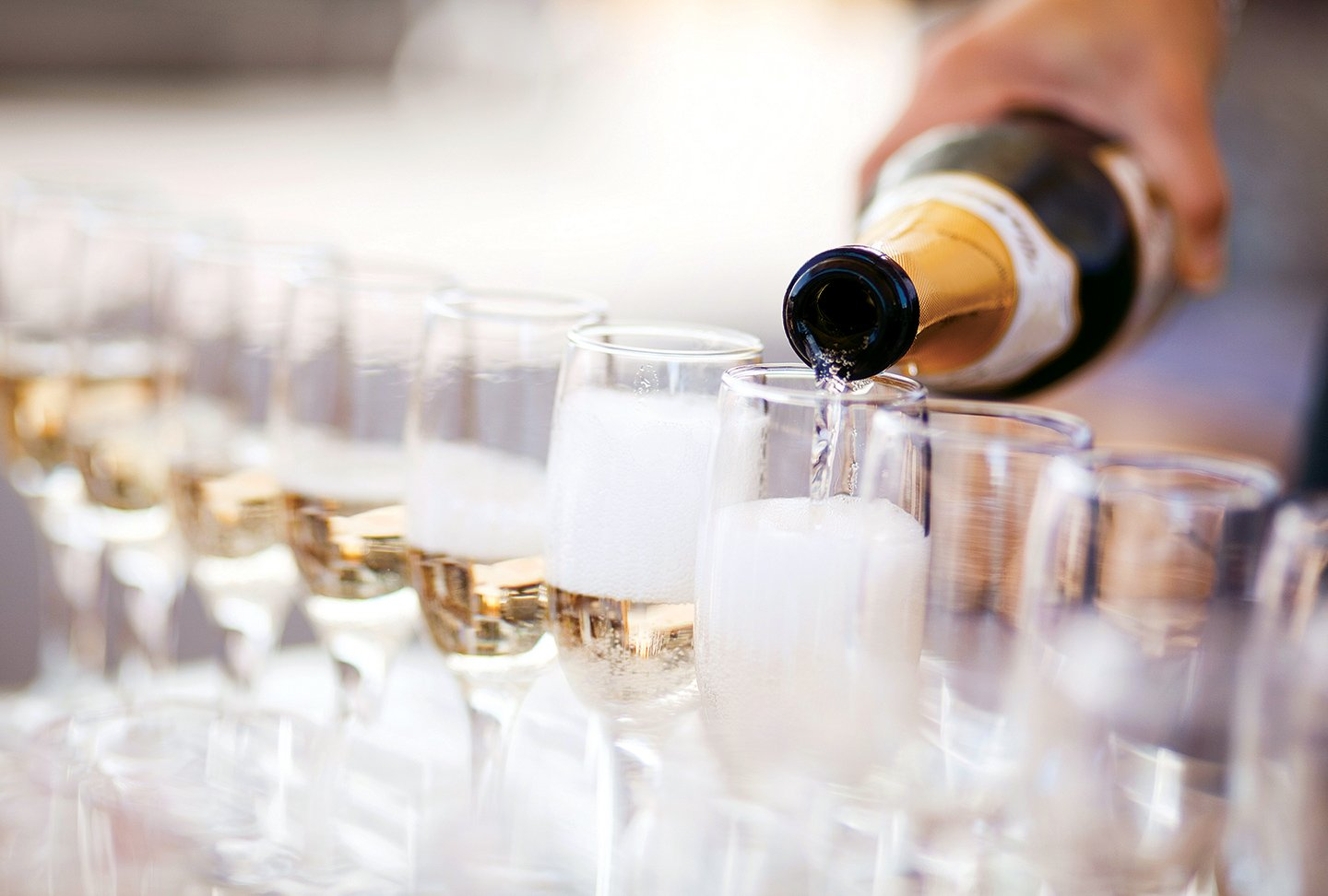 A long row of champagne flutes being filled