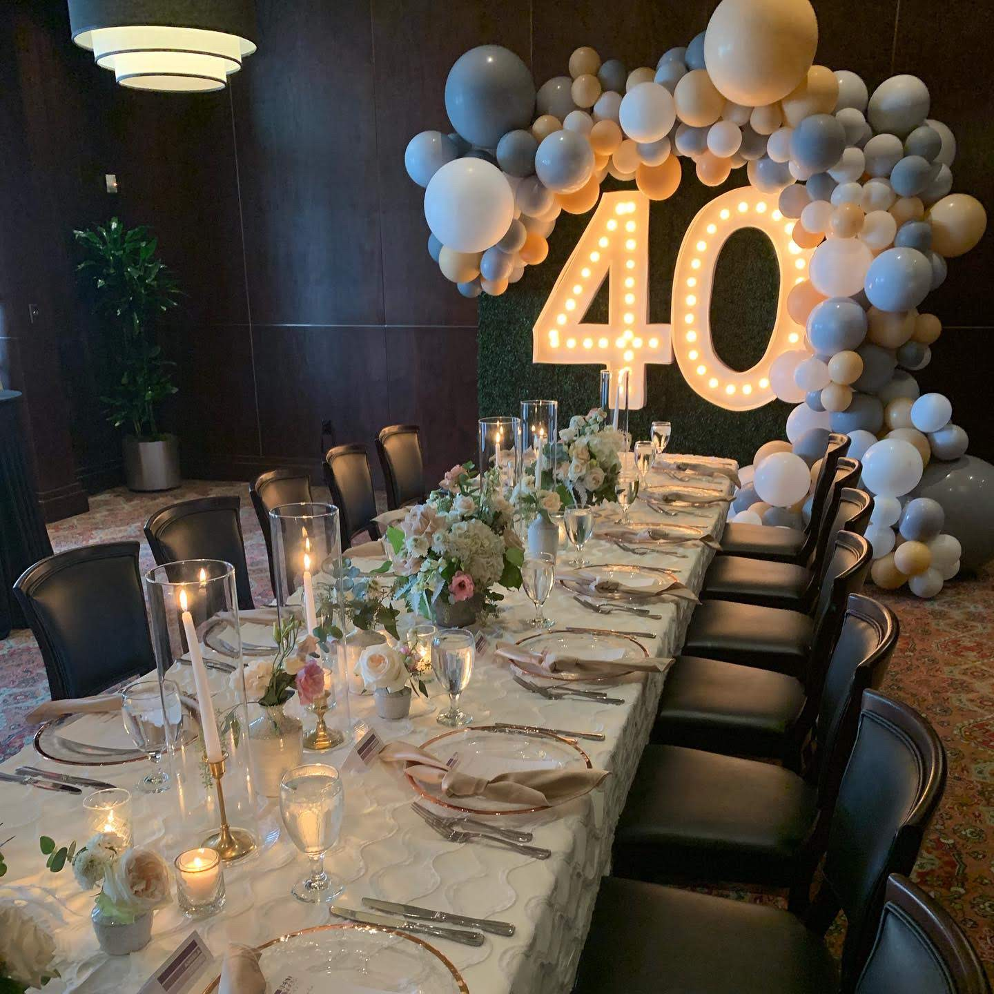 Truluck's Woodlands private dining event for a 40th birthday celebration. This includes white and cream linens with gold accents to include gold rimmed table chargers, gold candle sticks encased in glass with white taper candles. On the back wall is a green hedge with 5' lit up