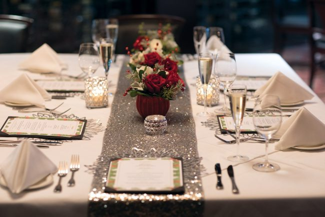 picture of private dining holiday floral centerpiece with red and white roses and holiday greenery