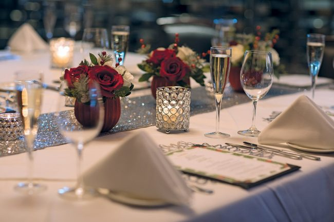 picture of private dining holiday decor with silver table runner, fresh flowers that include red and white roses and holiday greenery, crystal candles, specialty menus