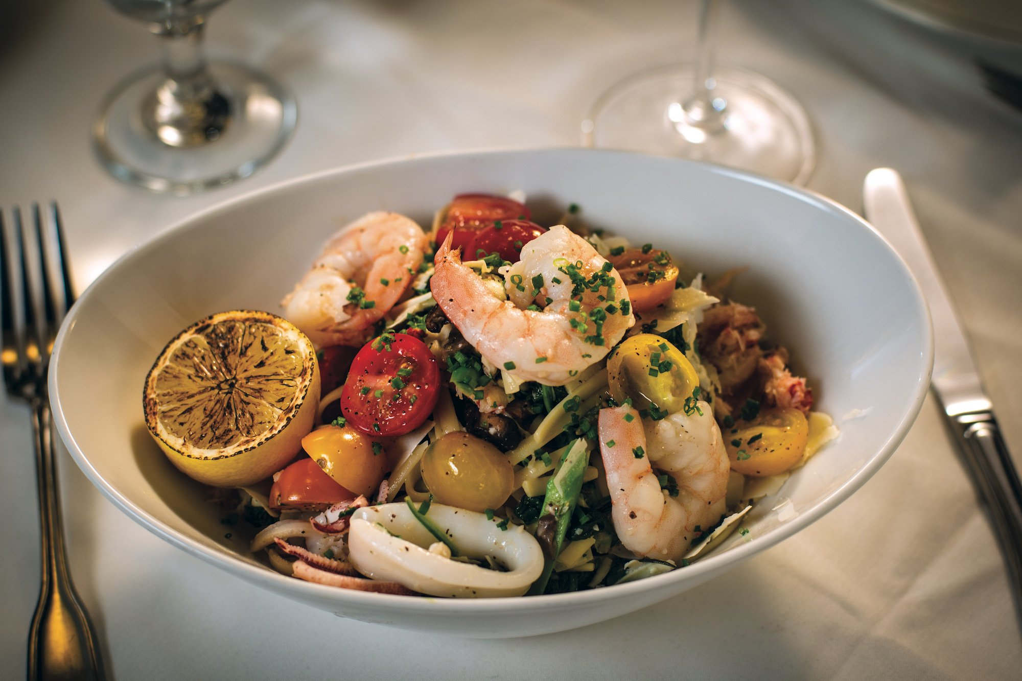 Shrimp pasta dish with heirloom tomatoes and chives, served with a fresh lemon ready to squeeze