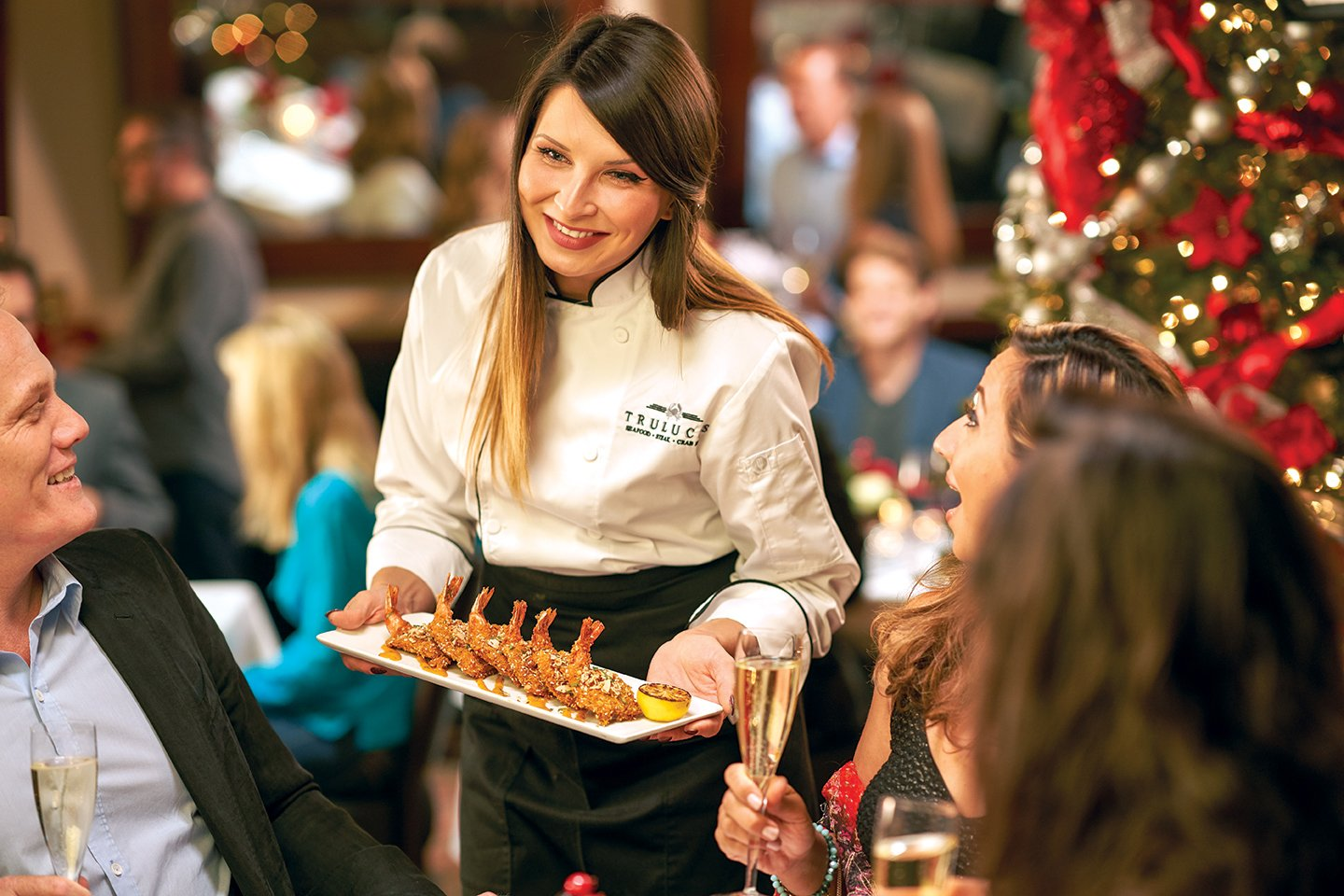 Private dining server serving appetizers to a table of guests during a holiday celebration