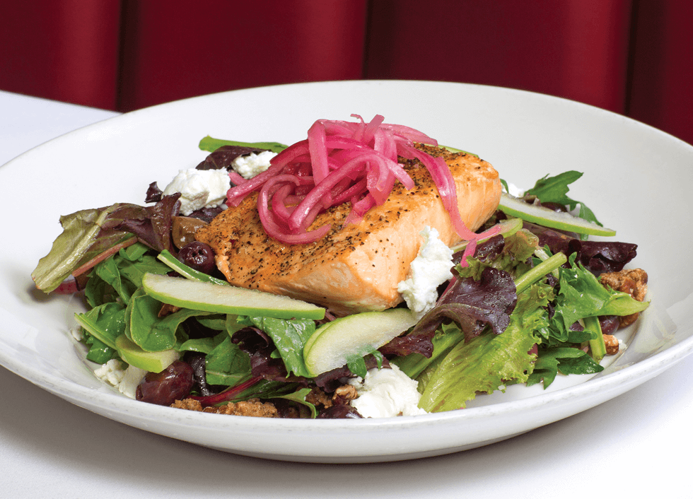 picture of Seared salmon resting on a bed of field greens with kalamata olives, pickled red onion, goat cheese, spiced pecans, and granny smith apples