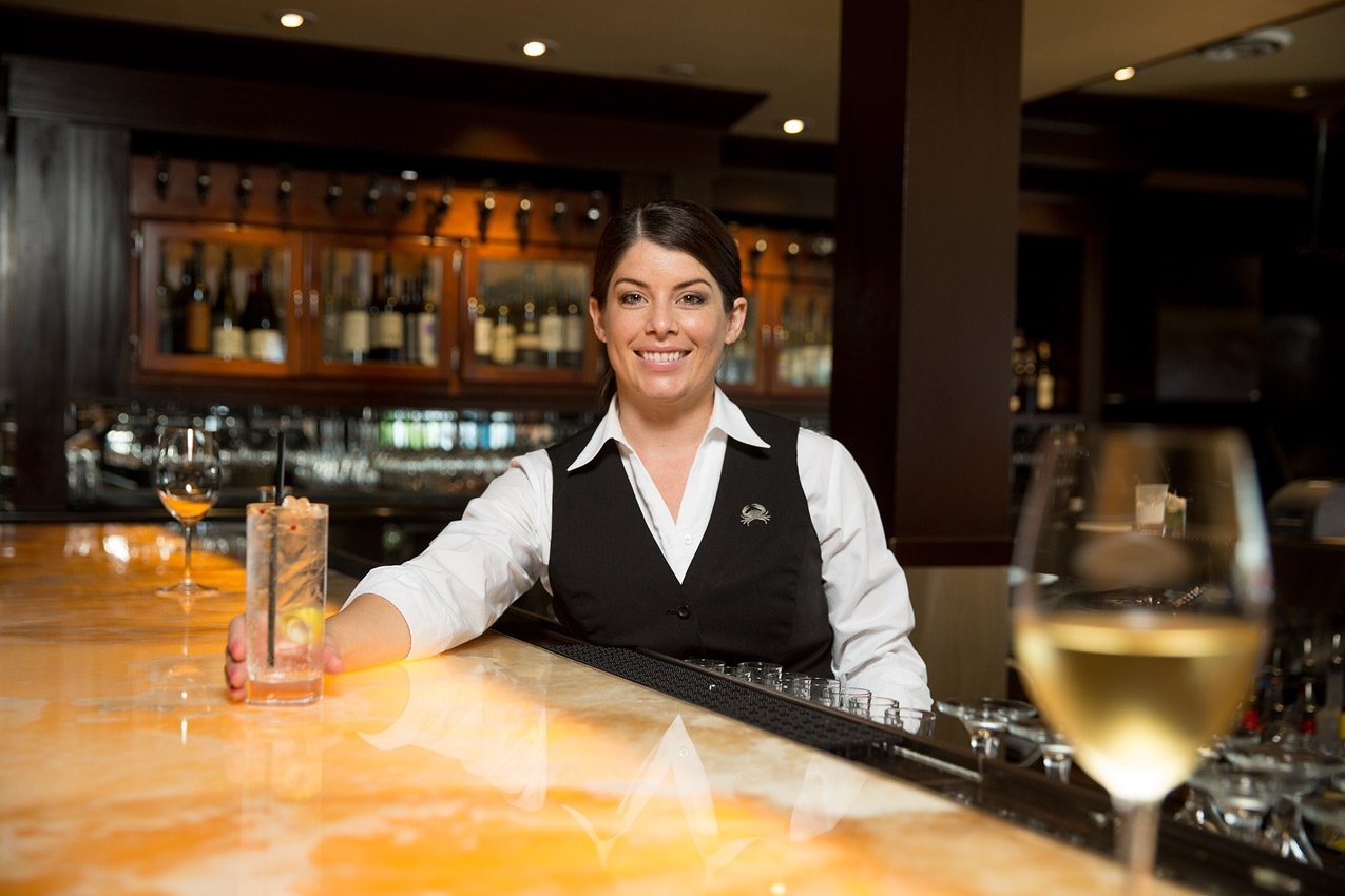 Truluck's bar tender smiles while serving a cocktail