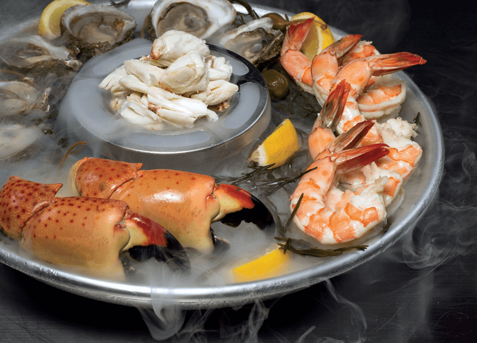 Chilled Seafood Celebration Dish: fresh crab claws, jumbo shrimp, and oysters circle around a pile of fresh crab, all lying on ice and with fresh lemon wedges ready to squeeze