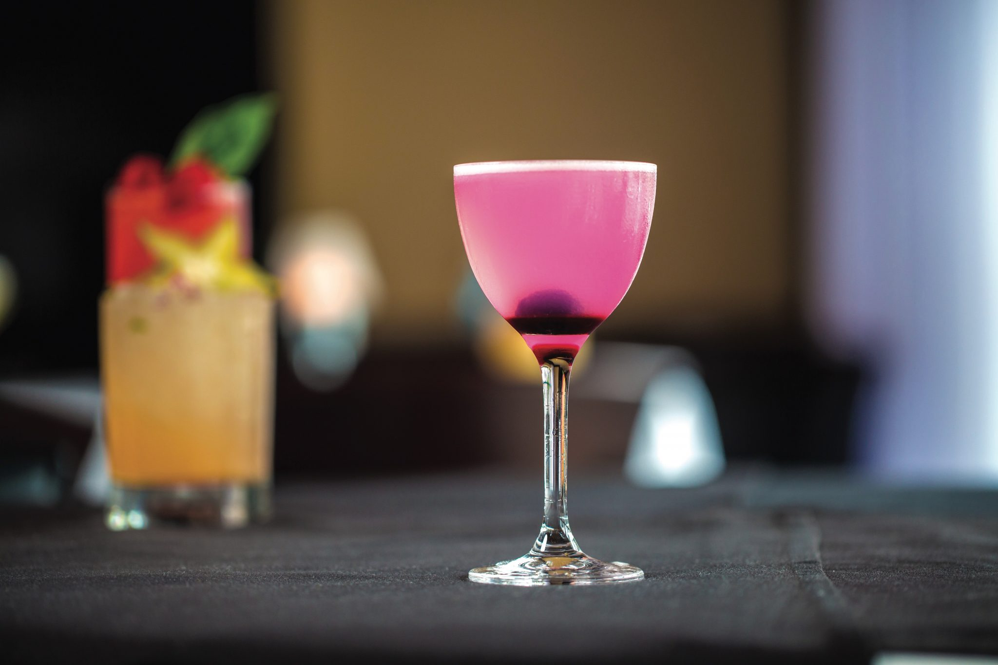 Bright pink drink in a stemmed cocktail glass with a berry in the bottom