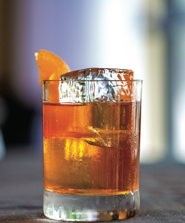 Old fashioned poured in a cocktail glass with a large block of ice and an orange rind