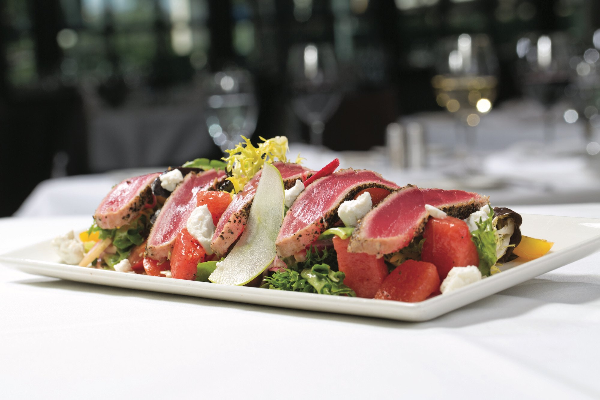 Pepper-crusted tuna lying on top of greens, tossed with watermelon, tomato, shaved red onions, and goat cheese