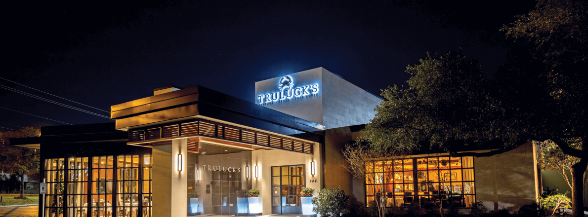 Truluck's restaurant in the nightime, lit with warm light from the inside and with a glowing logo