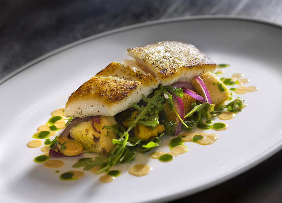 Miso Glazed Seabass Dish: Piece of fresh seabass lies on top of a bed of arugula, seasoned potatoes, and red onion. The fish is surrounded by sauces
