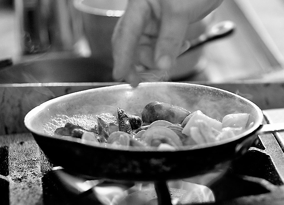 Chef seasons a pan of mussels sizzling on a stove