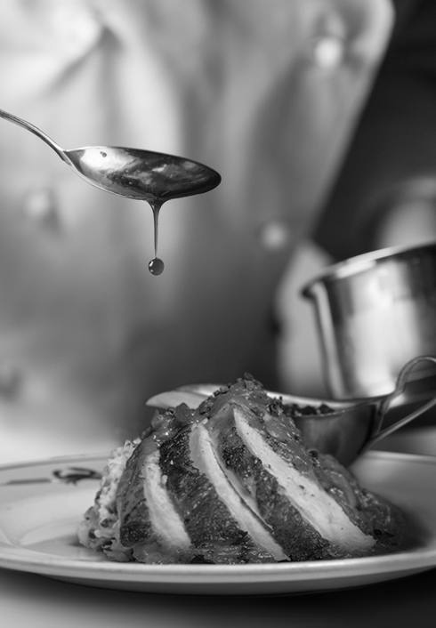 Sauce being drizzled over a plate of sliced turkey