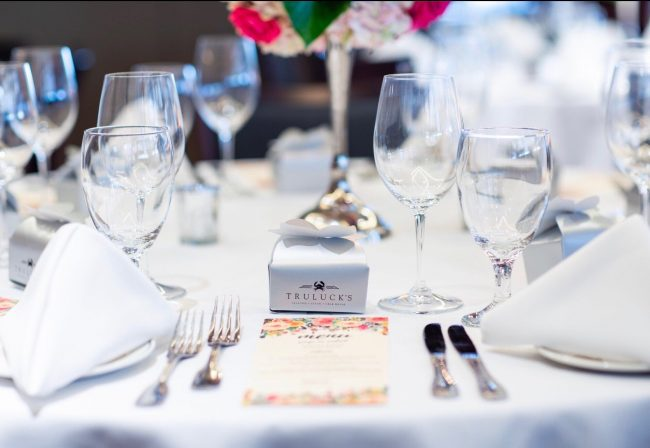 picture of Truluck's private dining table dressed in all white with a take away box of chocolates in a silver Truluck's box.