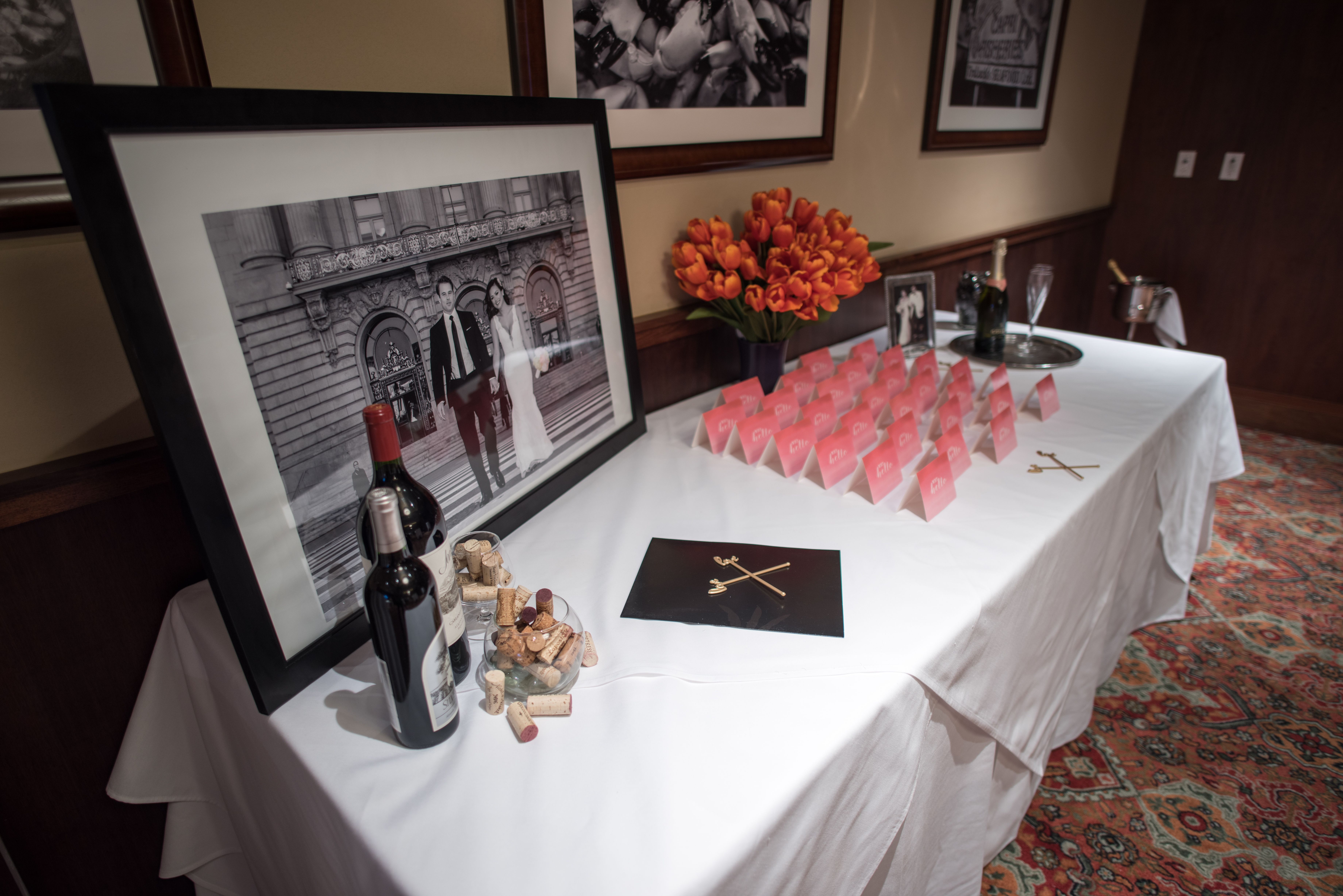 Truluck's Dallas private dining room table display with photo of brde and groom and place cards. this table is dressed with wine bottles and a bouquet of orange tulips