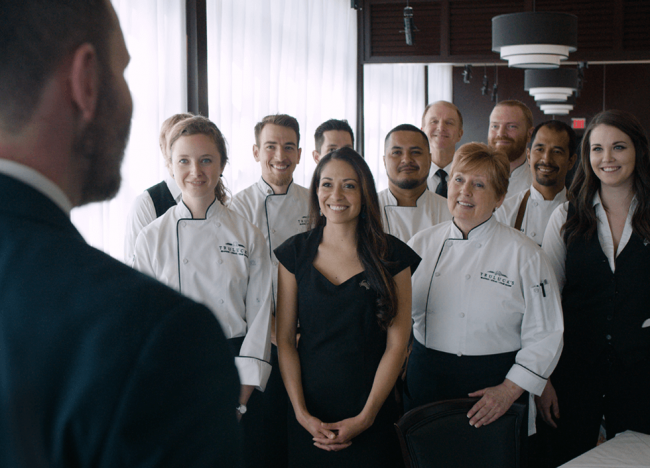 Team of Truluck's staff and chefs smile while listening to head manager
