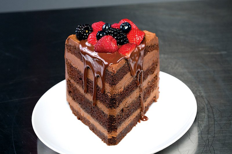 Chocolate malt cake with chocolate malt cream cheese icing drizzled with chocolate ganache and topped with strawberries, blueberries and blackberries