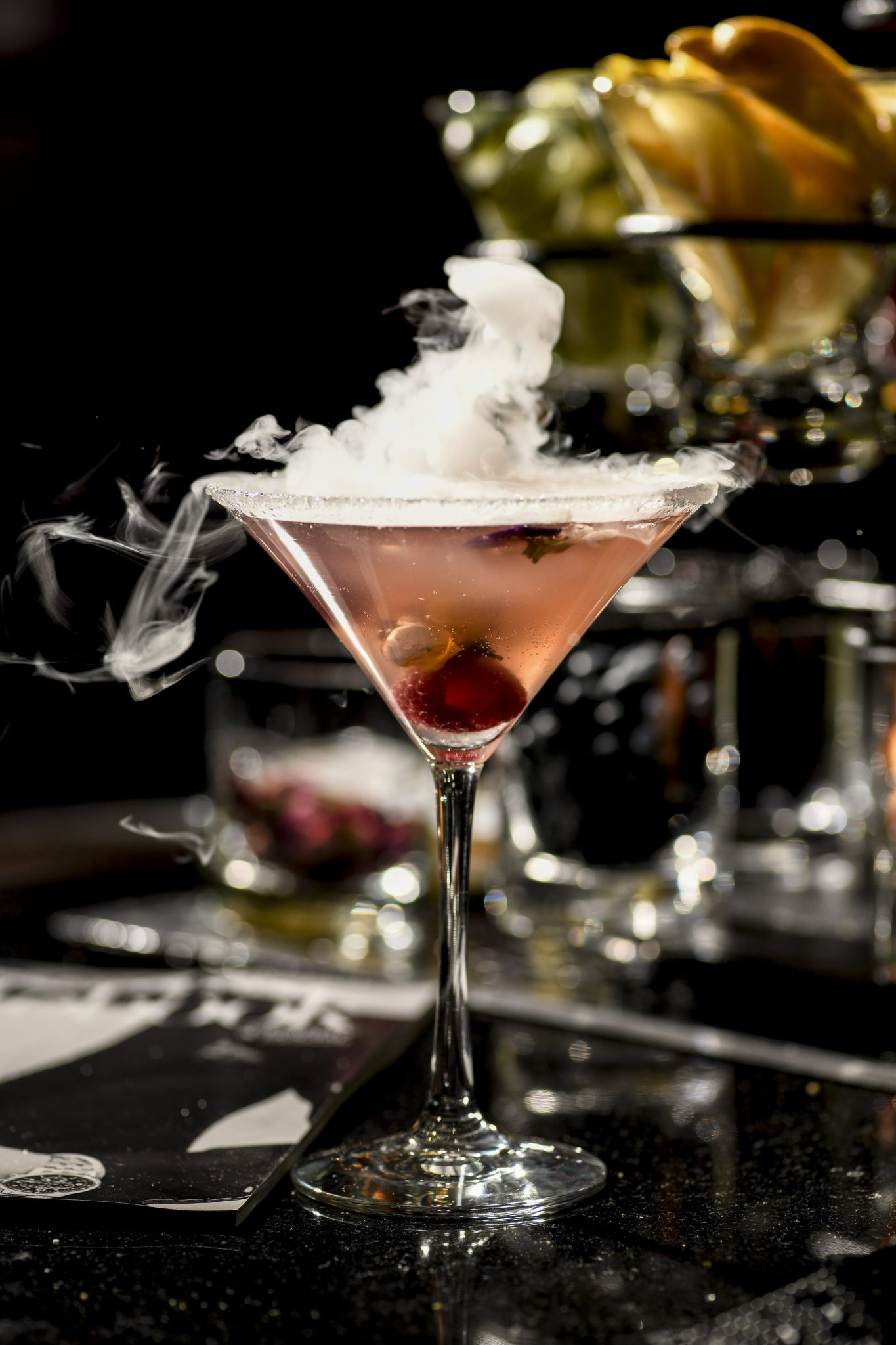 Cocktail in a martini glass with smoke lifting off the top