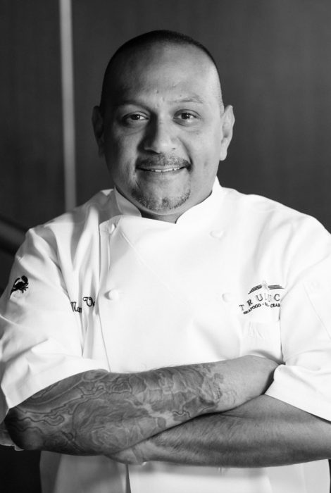 Manuel Vera smiling in his chef's apron