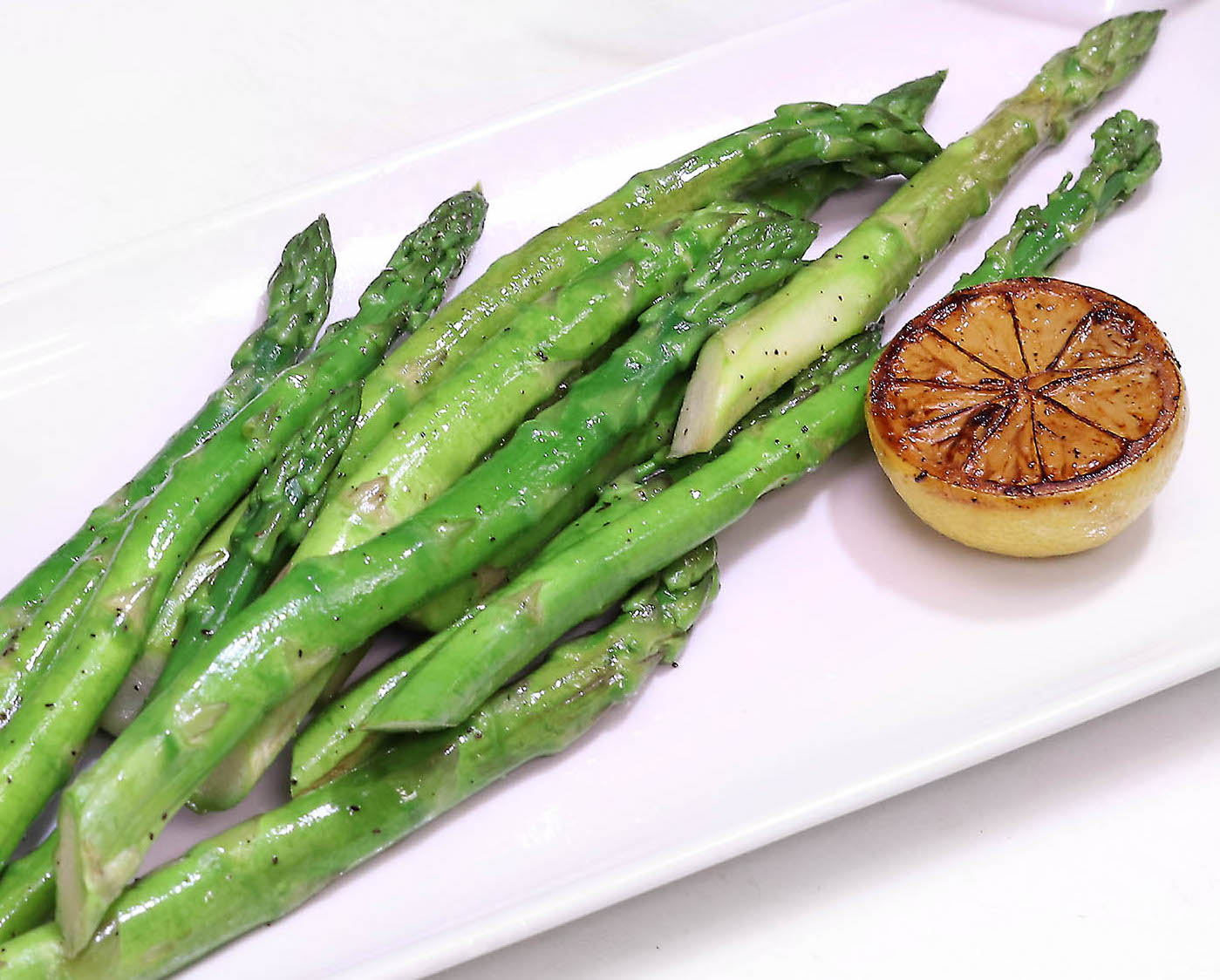 picture of Asparagus side item garnished with a lemon.