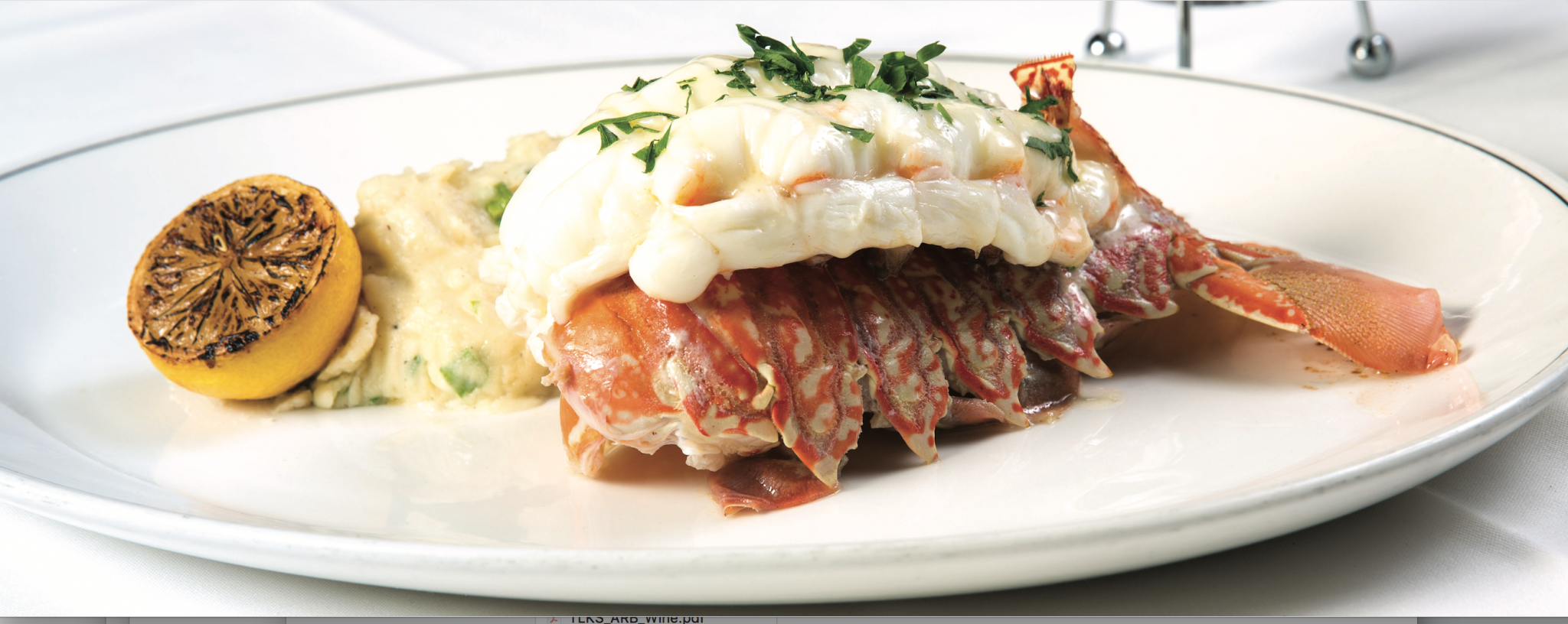 picture of SOUTH AFRICAN LOBSTER TAIL renowned worldwide for its sweetness and served with parmesan mashed potatoes. Garnished with a lemon.