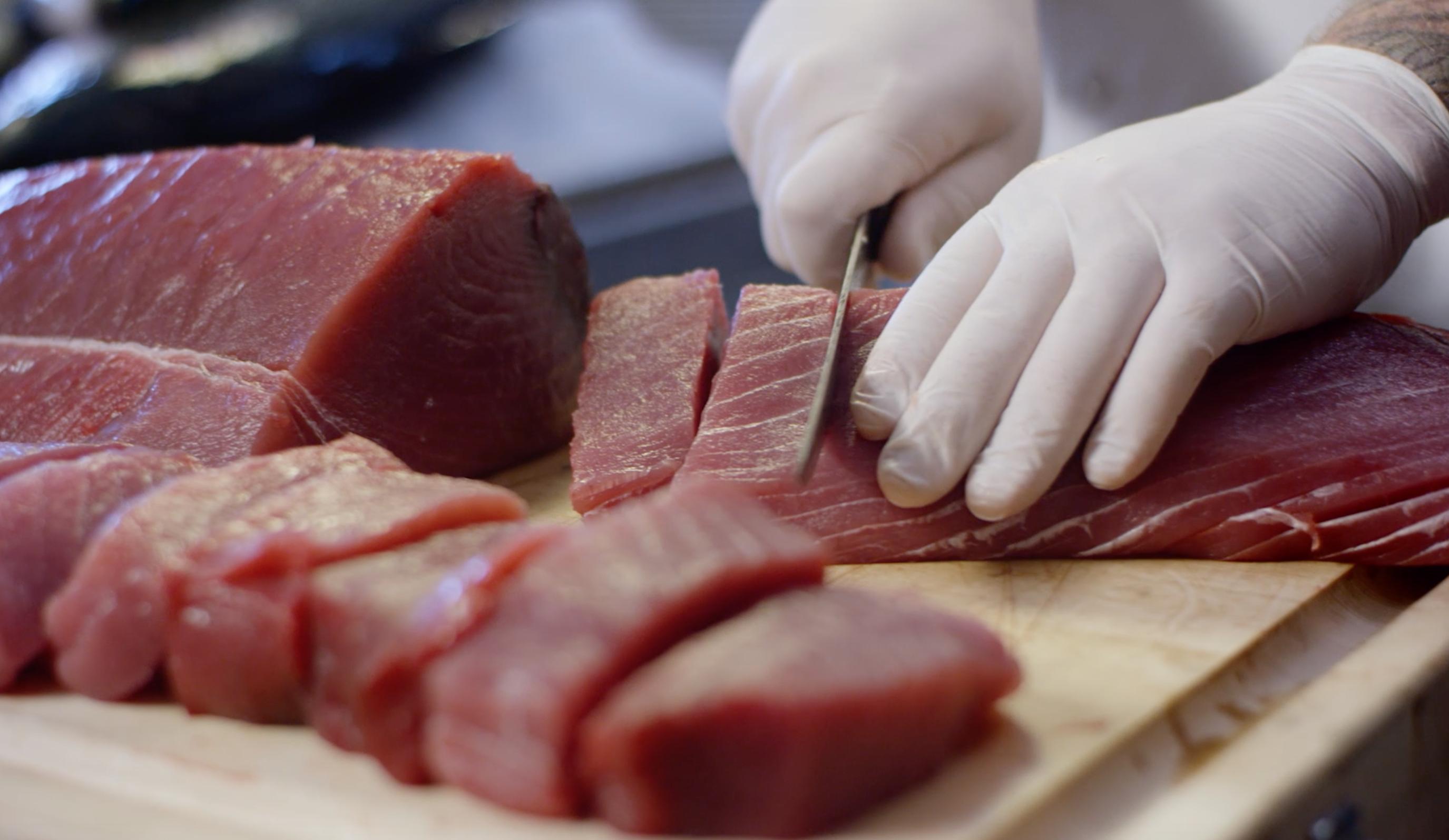 Chef cutting fresh ahi tuna on a cutting board with gloved hands.