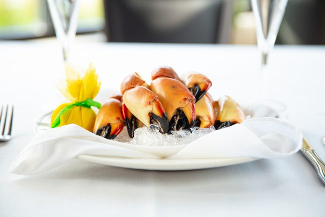 picture of Florida stone crab claws on ice with a wrapped lemon