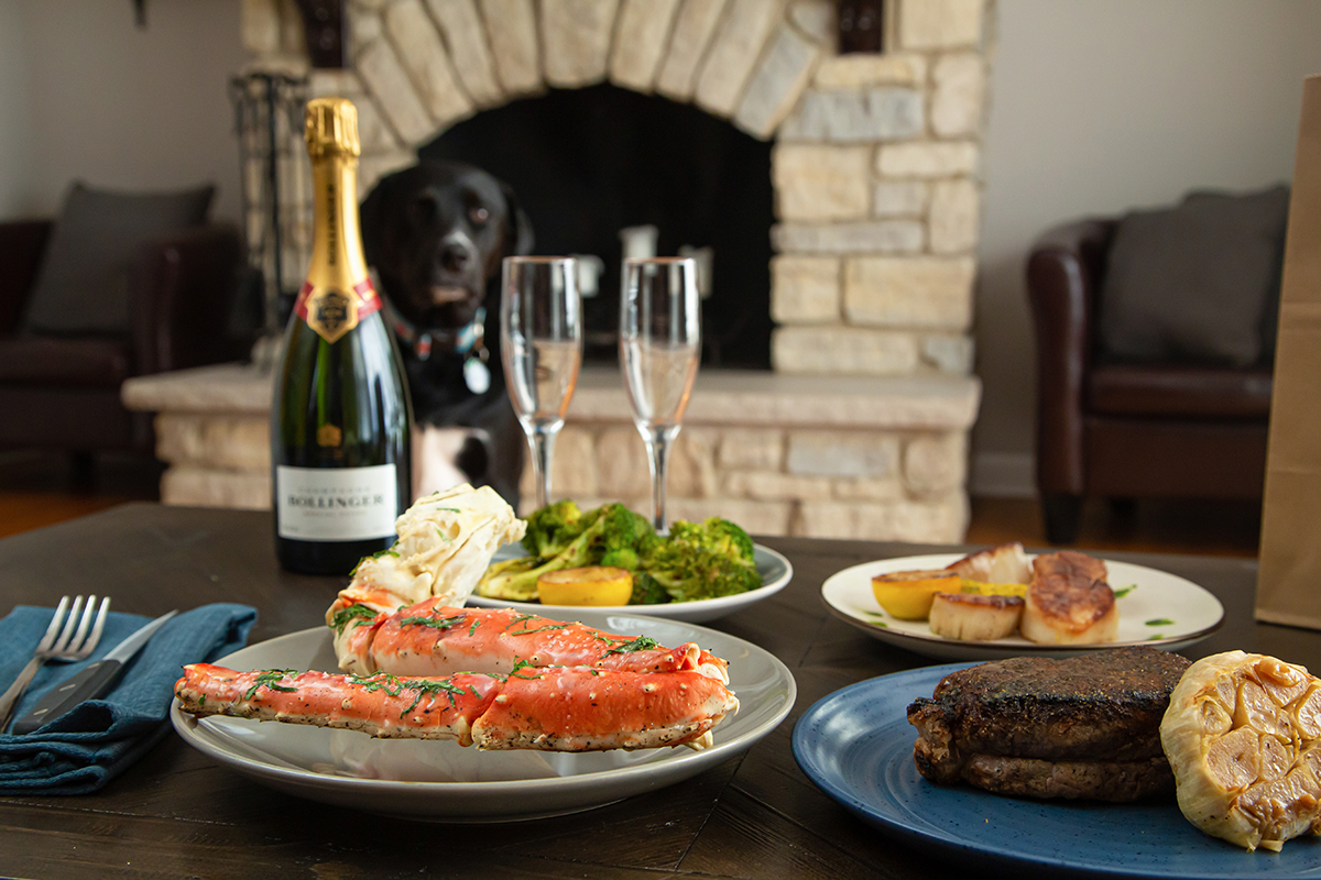 Curbside service at home. Photo of prime king crab leg, New York Strip, Broccoli, New-England Scallops and Bollinger Champagne with two champagne flutes. Our favorite dog, Yankee, is anxiously standing by in case there are any leftovers from this curbside service experience.