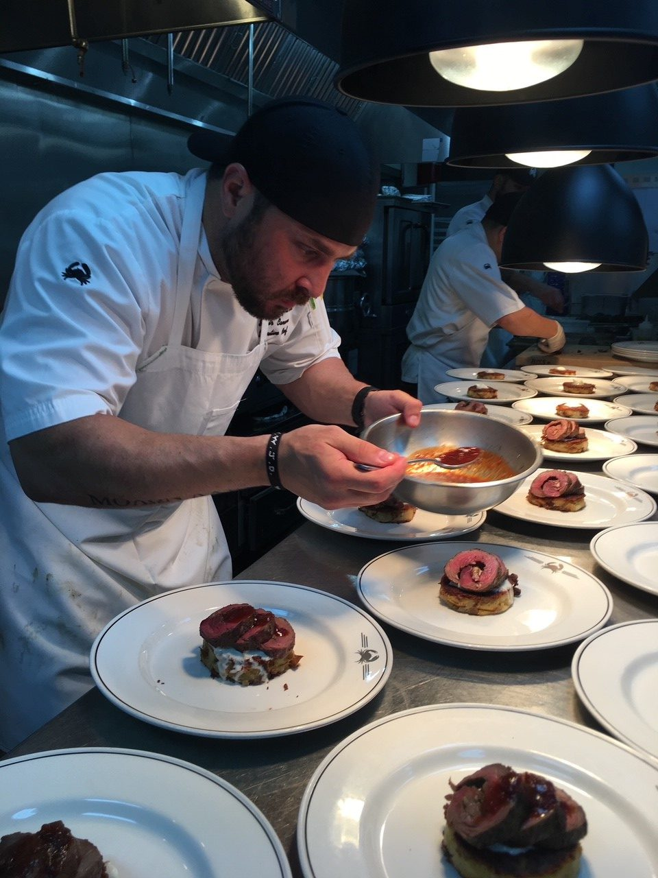 picture of Chef Samir Canaan plating food for a private event.