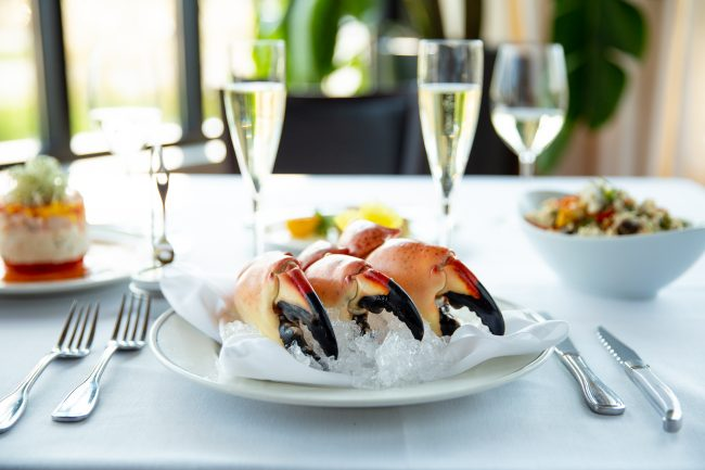 picture of Florida Stone Crab Claws on ice in the Truluck's dining room. Paired with crab Napoleon, crab fried rice and champagne.